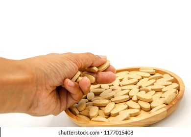vitamin C pill drug in wood bowl catch by hand on white background