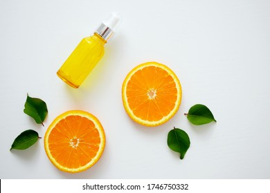 Vitamin C serum in cosmetic bottle with dropper and slices of orange on white background. Organic bio cosmetics with vitamin C. Homeopathic essential oil, nutritional supplements. Flat lay minimalism.