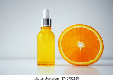 Vitamin C serum in cosmetic bottle and half of orange on white background. Organic SPA cosmetics with herbal ingredients. Citrus essential oil, cosmetics aromatherapy. Flat lay.