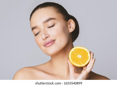 Vitamin C for skin. Delighted young pretty woman with closed eyes holding orange half over grey background - Shutterstock ID 1655540899