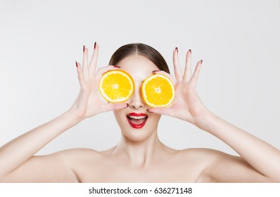 Vitamin C. A young woman holding two half oranges isolated white background