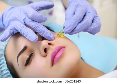 Vitamin in cosmetic ampoule. Doctor gets his hands beautician vitamin serum to the face of a beautiful woman.