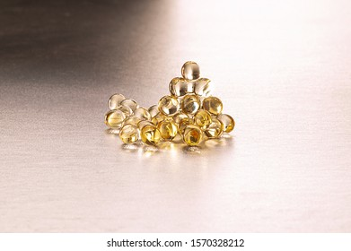 Vitamin D, Vitamin D3 soft capsules on a silver background.
