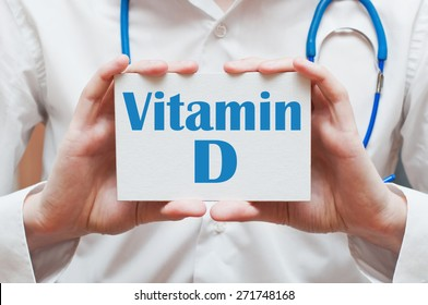 Vitamin D written on a card in doctors hands