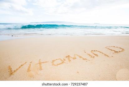 Vitamin D written in the sand at a tropical beach