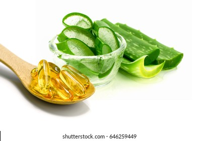 Vitamin E capsules and sliced Aloe Vera on white background.