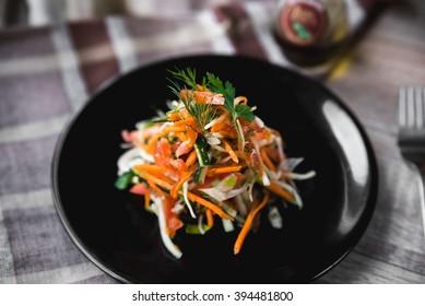 Vitamin fresh vegetable salad julienne on a black plate