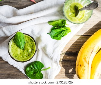 Vitamin green smoothie with spinach leaves, banana and peanut milk, clean eating,on gray wooden background