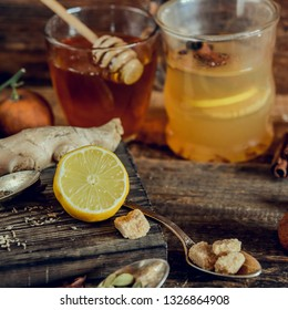 Vitamin healing tea with lemon and honey, ginger and spices on wooden background in rustic style. The concept of spring beriberi and colds. Square image.