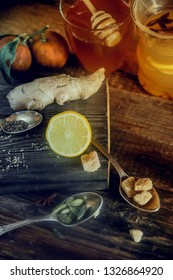 Vitamin healing tea with lemon and honey, ginger and spices on wooden background in rustic style. The concept of spring beriberi and colds.