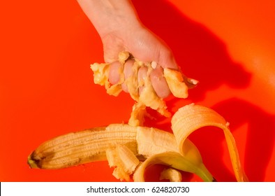 Vitamin and healthy eating. Female hand squeezing juice or squash from banana, ripe mellow fruit and peeled yellow skin on bright orange background