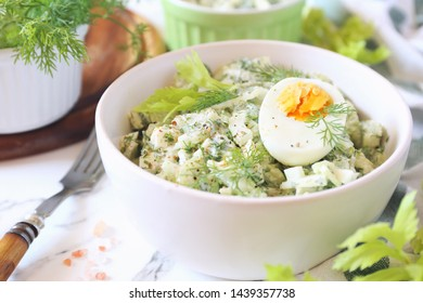 Vitamin light vegetable salad with dill, celery, eggs and Greek yogurt on wooden background