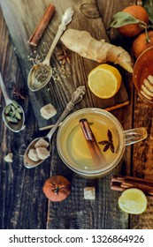 Vitamin medicinal tea with lemon and honey, ginger and spices on wooden background . The concept of spring beriberi and colds.