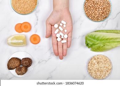 Die Vitamin-Nährstoffpillen auf der Hand, Naturmineralische Medizin, Bio-Früchte, Vollkorngetreide und Gemüse, gesunde Kosmetiknahrung.