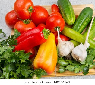 Vitamin set of vegetables from the red ripe tomatoes, orange and yellow peppers and  garlic with green sprigs of fresh