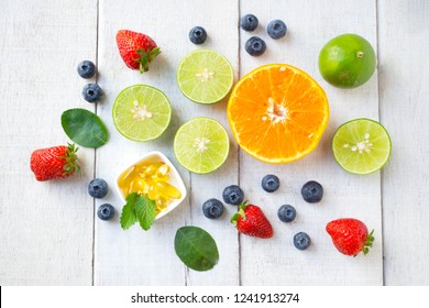 Vitamin supplement with healthy fruits blueberry, strawberry, lime, and orange on white wood background.Top view.