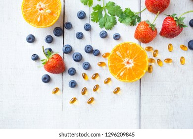 Vitamin supplement with healthy fruits blueberry, strawberry, and orange on white wood background.Top view.