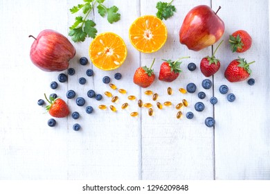 Vitamin supplement with healthy fruits blueberry, strawberry, apples, and orange on white wood background.Top view.