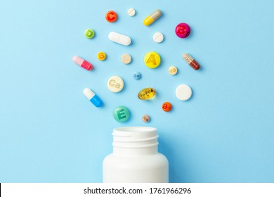 Vitamin tablets. Bottle with colored pills on blue background. Multivitamins.