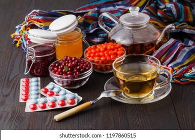 Vitaminic healthy sea buckthorn tea in small glass tea pot with fresh raw sea buckthorn berries and honey, folk medicina