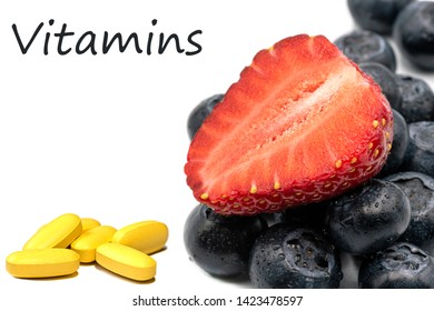 Vitamins in berries and tablets.Yellow pills, blueberries and strawberry on a white background close up.There are copy space on photo.