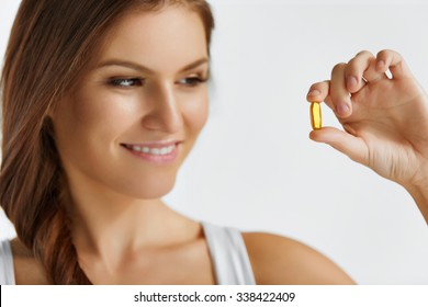 Vitamins. Close Up Of Happy Beautiful Girl With Pill With Cod Liver Oil Omega-3. Nutrition. Healthy Lifestyle. Nutritional Supplements. Sport, Diet Concept. Vitamin D, E, A Fish Oil Capsules.