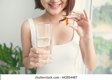 Vitamins. Close Up Of Happy Beautiful Girl With Pill With Cod Liver Oil Omega-3. Nutrition. Healthy Lifestyle. Nutritional Supplements. Vitamin D, E, A Fish Oil Capsules.
