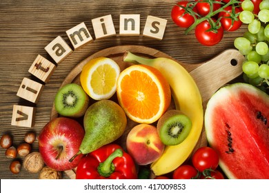Vitamins in fruits and vegetables. Natural products rich in vitamins as oranges, lemons, red pepper, kiwi, tomatoes, bananas, pears, apples, walnuts, watermelon, hazelnuts, peach and green grape