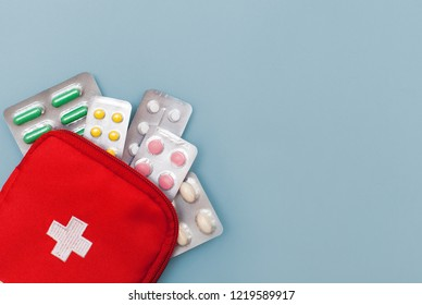 vitamins for health, multi-colored pills for diseases, narcotic drugs. Top view on the red first-aid kit with pills in a blister pack close-up on a blue background with space for text. Medications