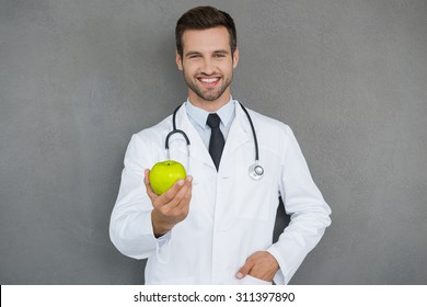 Vitamins are important for health. Cheerful young doctor in white uniform stretching out green apple and smiling while standing against grey background