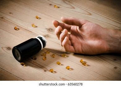 Vitamins overdose concept - passive hand on floor and spillage pills