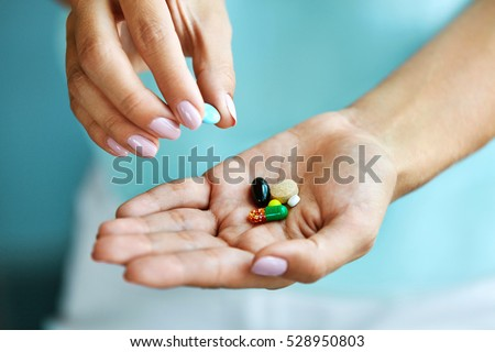Vitamins And Supplements. Closeup Of Female Hand Holding Variety Of Colorful Pills On Palm. Close-up Of Woman Fingers Taking Medication Tablets, Capsules From Hand. Medicine Concept. High Resolution
