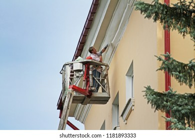 Vitebsk, Belarus  - August 05, 2013: Woman in bucket at height painting facade of building in Vitebsk