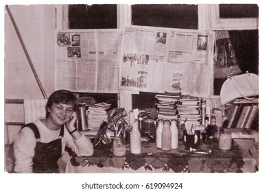 VITEBSK, BELARUS - CIRCA 1988: Cheerful student in unimproved room of dormitory of medical institution after settling, Vitebsk, Belarus