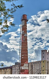 Vitebsk, Belarus - July 7, 2018: One factory smokestack tube against cloudy sky.