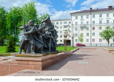 "VITEBSK, BELARUS - MAY 22, 2017: Fragment of memorial ""Liberators of Vitebsk - Soviet soldiers, partisans and underground fighters"". Unknown people are walking down street"