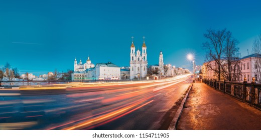 Vitebsk, Belarus. Panorama Of Evening Or Night View Of Famous Landmarks Is Assumption Cathedral, Church Of Resurrection Of Christ And Old Town Hall In Street Lights Illumination. Traffic Light Trails