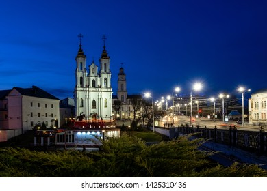 Vitebsk, Belarus. Panorama Of Evening View Church Of Resurrection Of Christ And Old Town Hall In Street Lights Illumination.