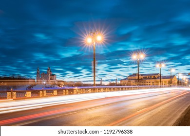 Vitebsk, Belarus. Traffic On Kirowski Bridge And View Of Assumption Cathedral Church In Upper Town On Uspensky Mount Hill In Evening Or Night Illumination At Winter.