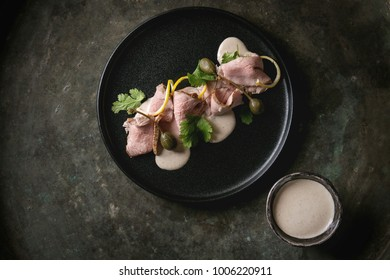 Vitello tonnato italian dish. Thin sliced veal with tuna sauce, capers and coriander served on black plate over old dark metal background. Top view, space