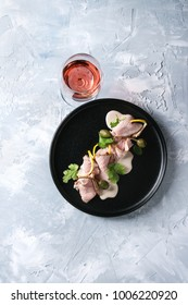 Vitello tonnato italian dish. Thin sliced veal with tuna sauce, capers and coriander served on black plate with glass of rose wine over gray texture background. Top view, space