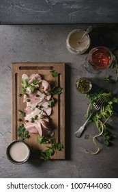 Vitello tonnato italian dish. Thin sliced veal with tuna sauce, capers and coriander served on wooden serving board, glass of rose wine and ingredients above on gray texture kitchen table. Top view