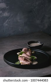 Vitello tonnato italian dish. Thin sliced veal with tuna sauce, capers and coriander served on black plate over dark texture background. Top view, space