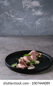 Vitello tonnato italian dish. Thin sliced veal with tuna sauce, capers and coriander served on black plate over gray texture kitchen table.