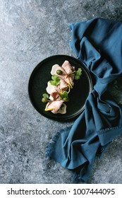 Vitello tonnato italian dish. Thin sliced veal with tuna sauce, capers and coriander served on black plate with blue textile over blue texture background. Top view, copy space