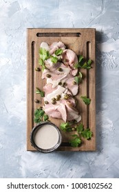 Vitello tonnato italian dish. Thin sliced veal with tuna sauce, capers and coriander served on wooden serving board over gray texture background. Top view, space