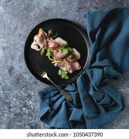 Vitello tonnato italian dish. Thin sliced veal with tuna sauce, capers and coriander served on black plate with blue textile over blue texture background. Top view, copy space. Square image