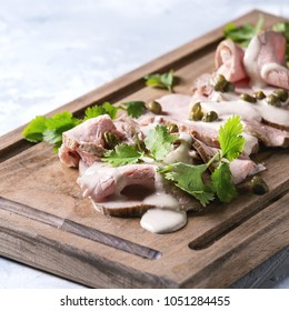 Vitello tonnato italian dish. Thin sliced veal with tuna sauce, capers and coriander served on wooden serving board over gray texture background. Square image