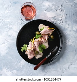 Vitello tonnato italian dish. Thin sliced veal with tuna sauce, capers and coriander served on black plate with fork and glass of rose wine over gray texture background. Top view, space. Square image