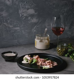 Vitello tonnato italian dish. Thin sliced veal with tuna sauce, capers and coriander served on black plate, glass of rose wine and ingredients above over gray texture kitchen table. Square image